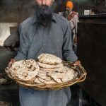Sikh with freshly made chapatis at the Golden Temple kitchen