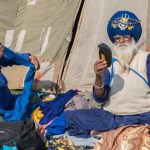 One-armed Nihang grooming himself at the Hollah Mahallah grounds while the other ties his turban