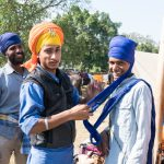 Helping to tie his friend's turban