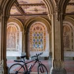 A lone bicycle in the Central Park passageway with lovely marble frescoed walls and columns, New York City