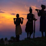 Silhouettes of warriors of the Hamer tribe in a village in the Omo Valley, Ethiopia at sunset.