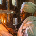 An orthodox priest reads his Bible Inside the cave monastery of Yimrihana Kristos, east of Lalibela, Ethiopia