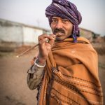 Man with Neem twig to clean his teeth.