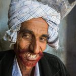 Man from the Little Pakistan region of Gujarat with hennaed beard and bad teeth