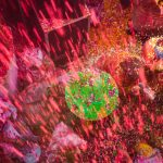 Strong colours of  Gulal powder and flower petals raining down at Widows Holi Festival, Mathura