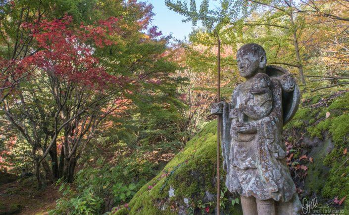 Buddhist stone statue at Jingon-ji with autumn leaves, in Nakatsu