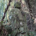 Stone Buddha statue in a wooded forest in Kunisaki