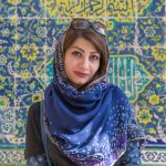 Portrait of an Iranian woman alongside a tiled wall in Isfahan.