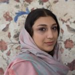 Portrait of an Iranian woman alongside a tiled wall at the Armenian church in Isfahan.