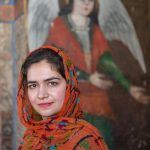 Portrait of an Iranian woman alongside a frescoe of an angel at the Armenian church in Isfahan.