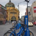 Blue bicycles, part of Melbourne's Bike Share parked outside Federation Square, with Flinders Street Station in the background