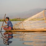 A fisherman with cone shaped net peddling boat on lake Inle