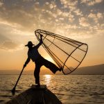 Leg-rowing fisherman on Inle Lake at sunset