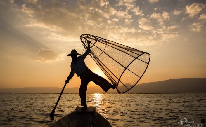Leg-rowing fisherman on Inle Lake at sunset