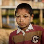 Burmese boy with thanaka powder, with his school behind him