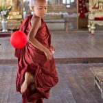A boy monk enjoys kicking a balloon about in the wooden monastery in Inle Lake