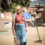 A Nepali woman winnowing rice in a Nepali viallge