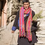 A Nepali man carrying offerings to a temple in Jharkot