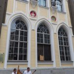 Musicians with ancient musical instruments basking in front of a lovely building in Tallinn