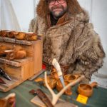 A craftsman with his handmade wooden products at the Jokkmokk Winter Market