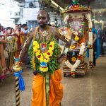A devotee with a chariot attached to his back with hooks in his back. Thaipusam 2015