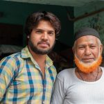 Muslim man with hannaed beard, with son, in Ramgarh, Rajasthan