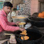 Man making fried sweet pancake, Mandawa
