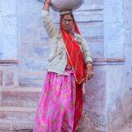Woman in Jodhpur balancing big pot of water