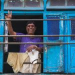 Man smiling from a window in Udaipur