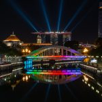 Reflections of a rainbow-coloured Elgin Bridge with the Marina Bay Sands Hotel laser lights shooting upwards to the sky.